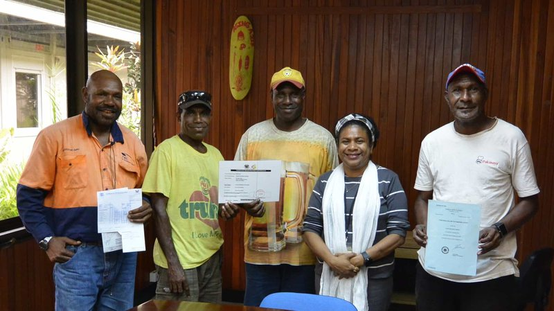 From L-R: Landowners of Utsiap Andrew Kising, Adam Gubu, Peter Sanga, and Paul Gabi showing their company documents to PNG Biomass Stakeholder Engagement Manager, Jessie Mitir, at the PNG Biomass Office