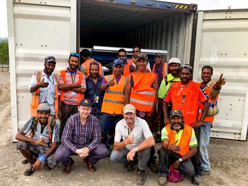 Carlos Hartwich with Garry Townley and the PNG Biomass forestry and planting team welcoming the arrival of the container with new equipment.