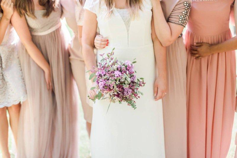 Bruid met paarsroze bruidsboeket en bruidsmeisjes in verschillende tinten roze jurken - House of Weddings