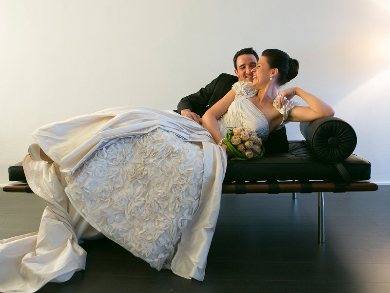 Bruidspaar op zwart lederen bank - Fotografie Kestelyn - House of Weddings