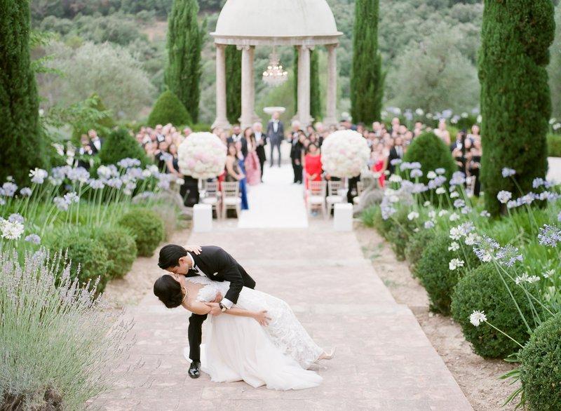 Bruidspaar met gezelschap ceremonie op de achtergrond - Maitha Lunde Photography - House of Weddings