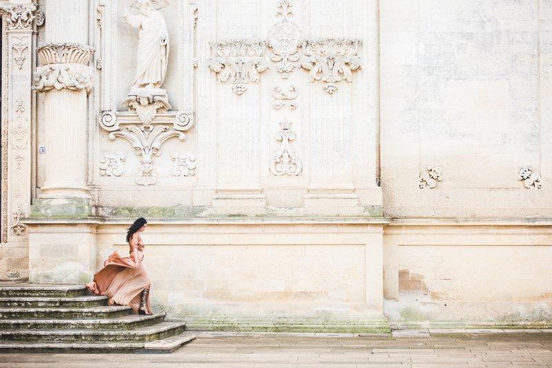 Bruid op trap bij details kerk in zachtroze tinten - Lux Photography - House of Weddings