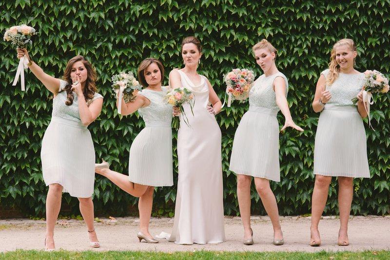 Bruid en bruidsmeisjes poseren voor groene haag voor foto - House of Weddings