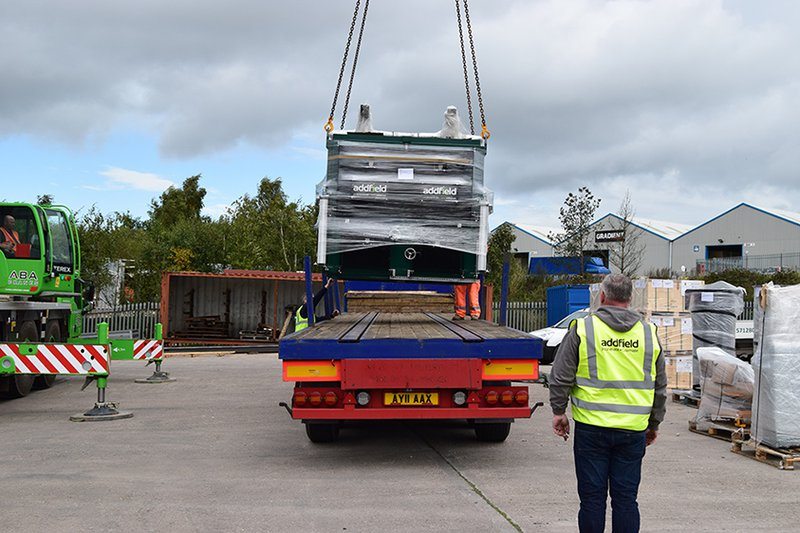 Loading a multi chambered pet cremator onto a flat bed truck by a crane to How to ship an incinerator internationally.