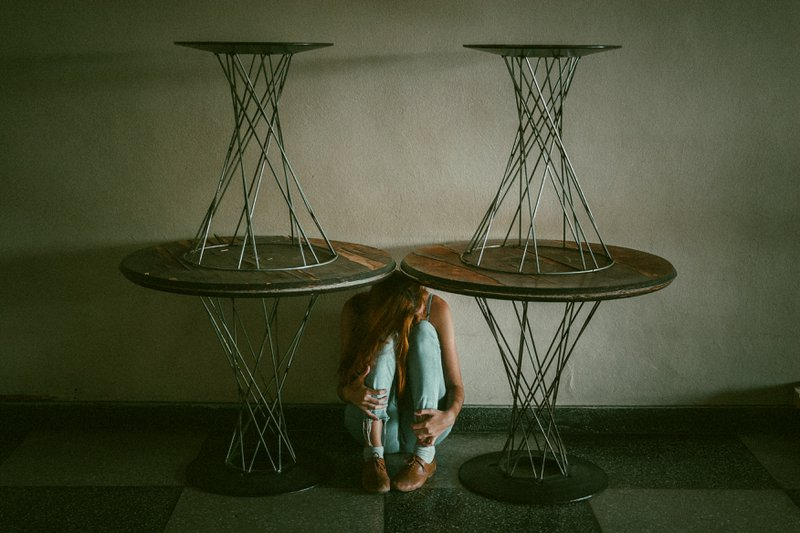 Woman under a table, feeling lost, unimportant , the result of imposter syndrome