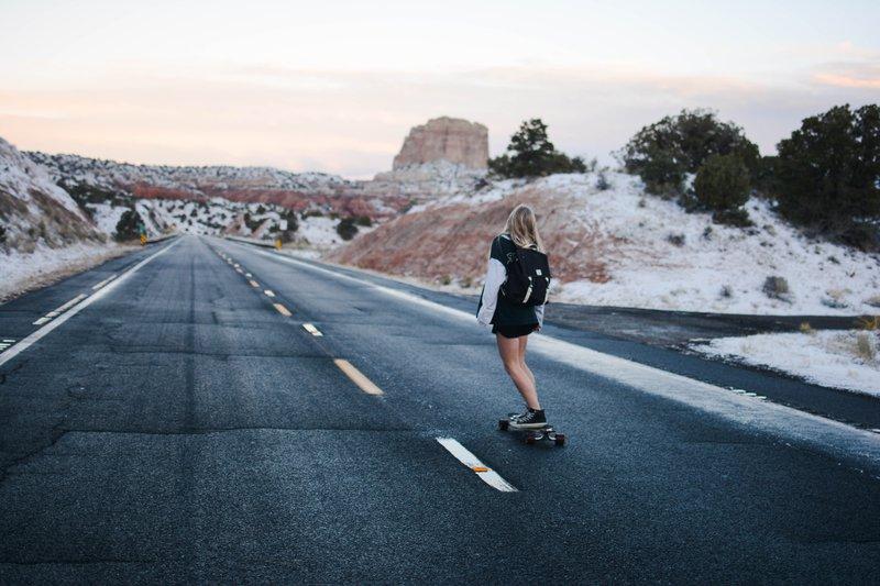 Meisje die op skateboard van berg rolt in mooi landschap