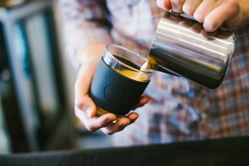 Barista pouring coffee into a glass reusable coffee cup