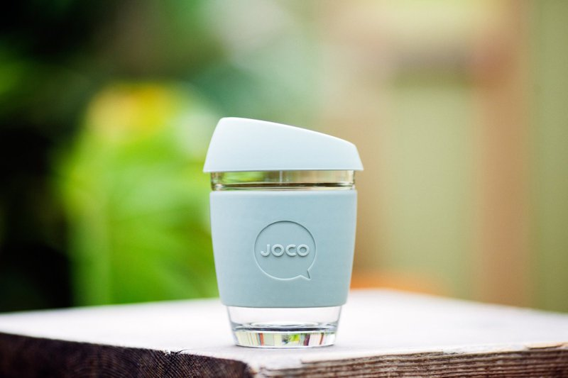 A pale blue JOCO glass reusable coffee cup on a table.
