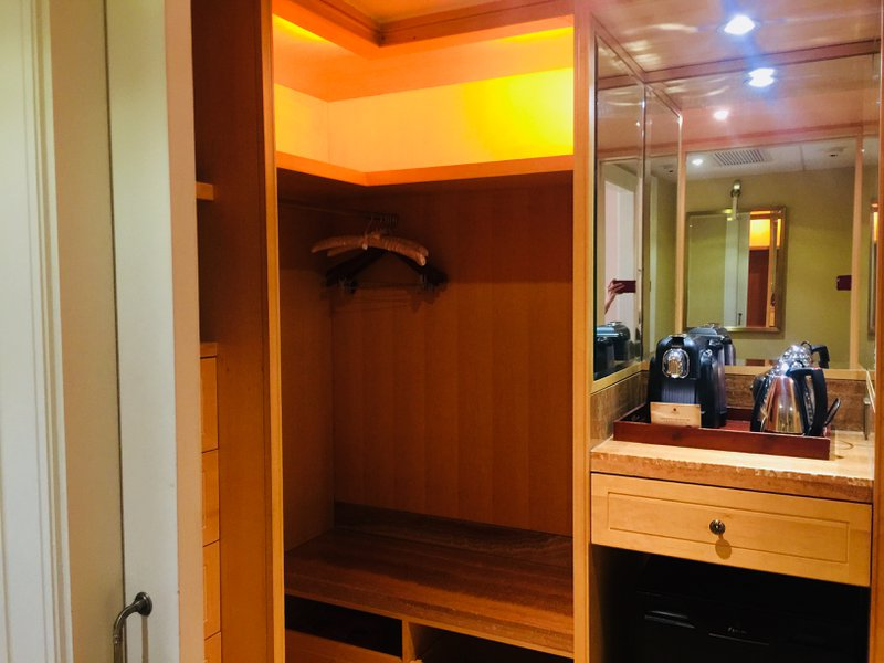 The Astor Hotel in Tianjin - Walk-in closet with an espresso machine and mini-bar