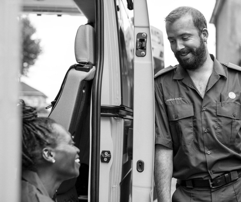 A smiling ambulance driver speaking with a woman