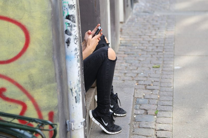 Person hidden behind wall, looking at phone