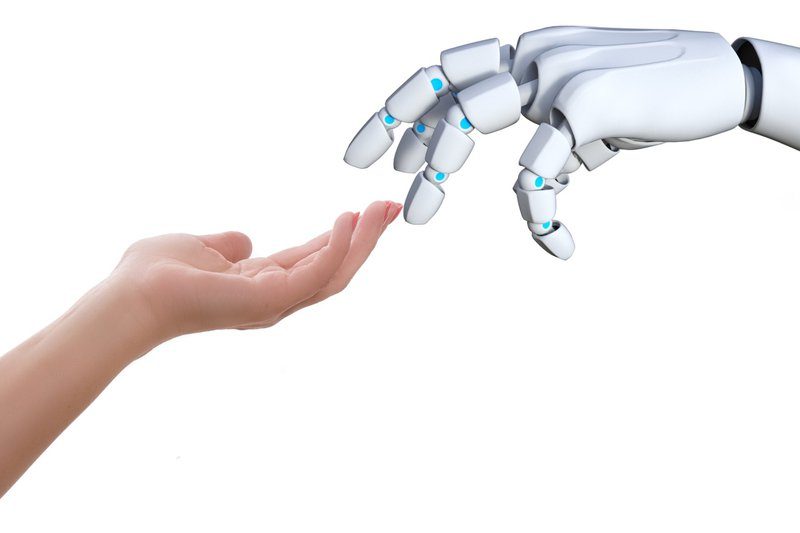 Human and robotic hands reaching out for one another