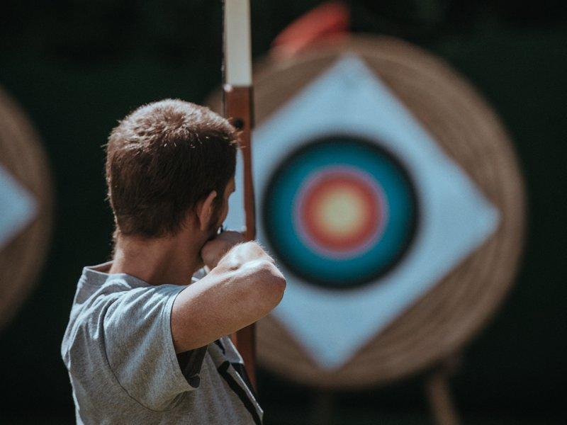 a man taking aim at a bulls-eye as a metaphor for a target market