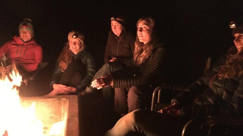 Women around campfire; headlamps