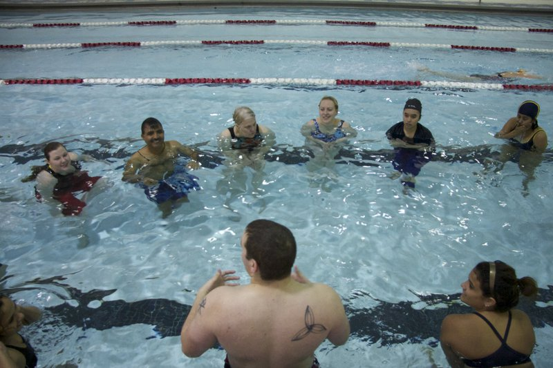 A group of 8 students gather around their swimming instructor during adult swimming lessons.
