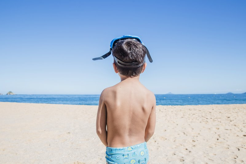 A boy looks out into the water from the beach.
