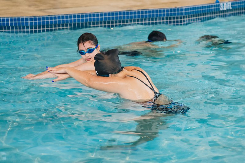 A swimming instructor demonstrates proper arm position to her student during her adult swimming lessons.