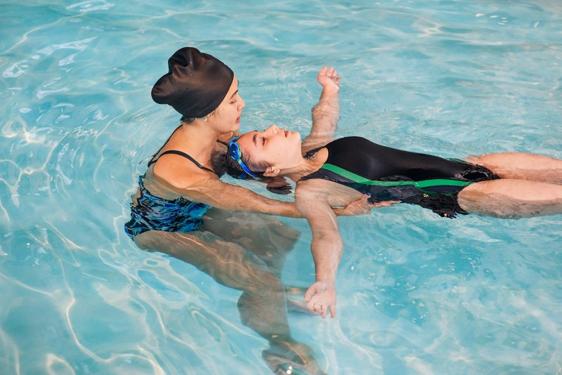 A female swimming instructor helps support a new swimmer settle into a back float during her adult swimming lessons.
