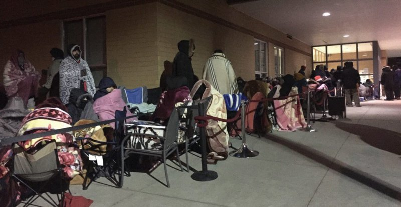 A long line of people wait outside of a community centre to register for kids swimming lessons.