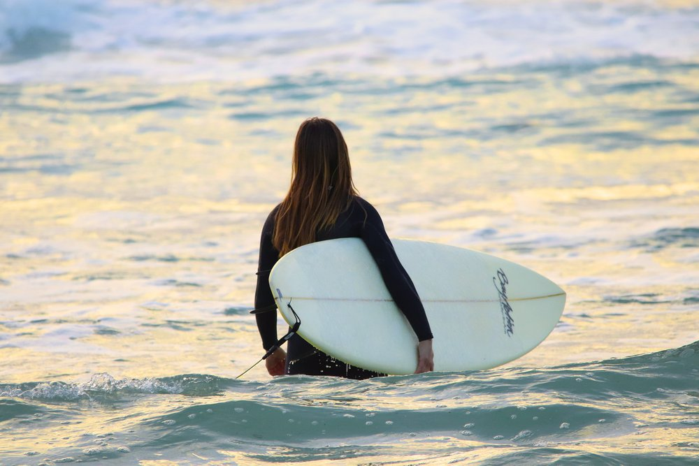 A woman in a wetsuit holding a surf board as she wades into the water.
