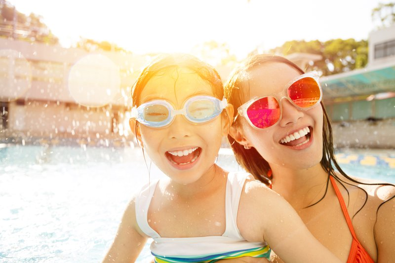 A young girl and her swimming instructor having fun at the pool.