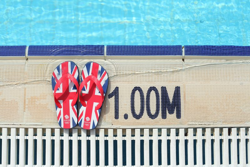 A pair of red, blue, and black Union Jack flip-flops sit by the pools edge.